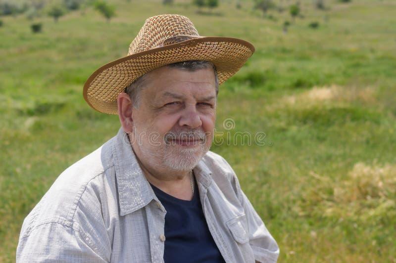 Porträt des glücklichen ukrainischen Bauers auf einer Frühlingsweide stockfotografie