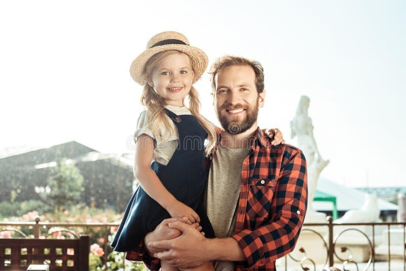 Porträt des glücklichen Vaters Tochter auf Händen und dem Schauen halten lizenzfreie stockfotografie