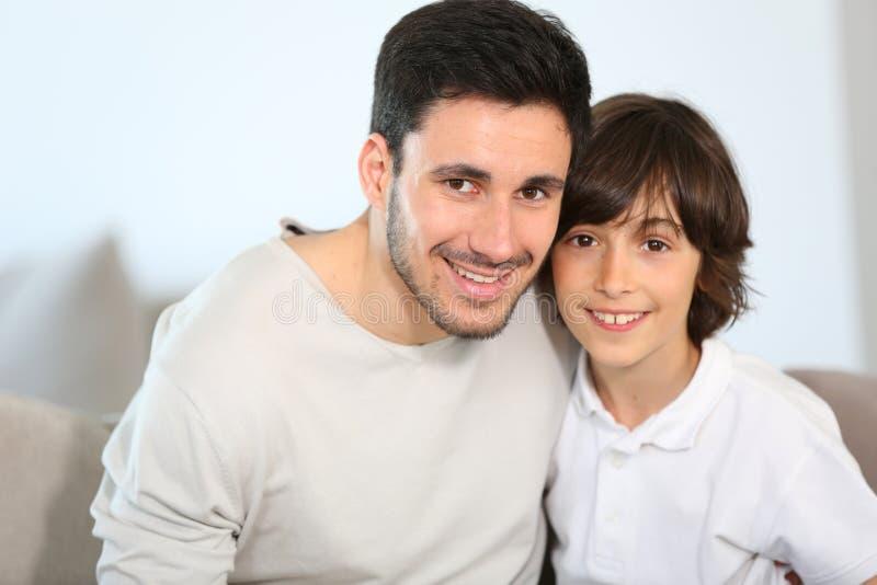 Porträt des glücklichen Vaters und des Sohns, die auf Sofa sitzt lizenzfreie stockbilder