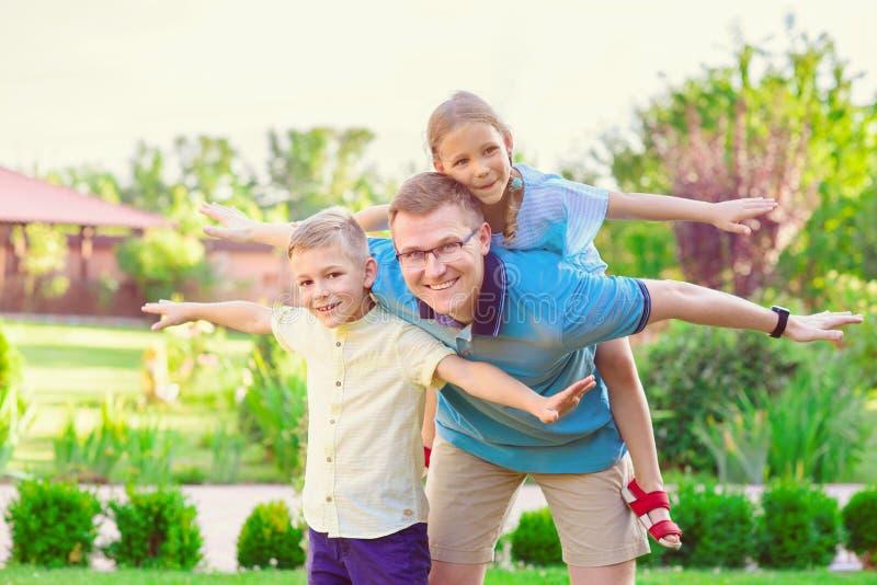 Porträt des glücklichen Vaters und zwei netten der Kinder, die an courty spielen stockfotos