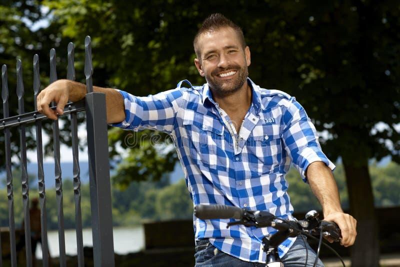 Porträt des glücklichen zufälligen Mannes auf dem Fahrrad im Freien stockbild