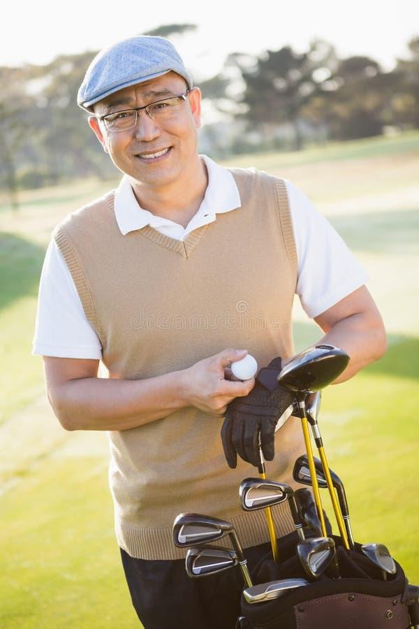 Porträt des Golfspielers aufwerfend mit seinen Golfausrüstungen stockfotos