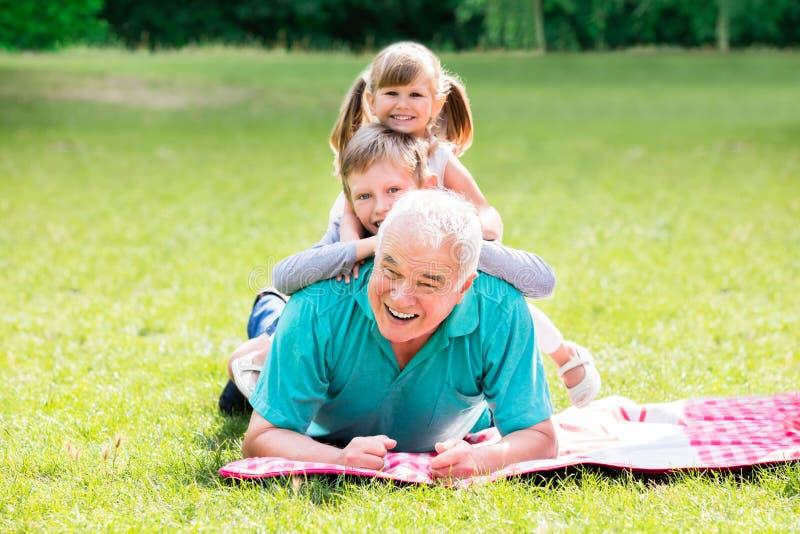 Porträt des Großvaters und der Enkelkinder, die auf Gras liegen stockbild