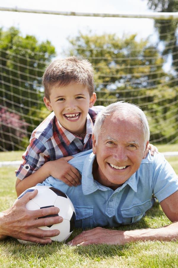 Porträt des Großvaters und des Enkels mit Fußball stockfotografie