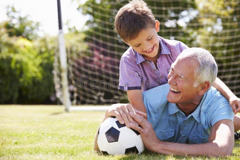 Porträt des Großvaters und des Enkels mit Fußball stockfoto