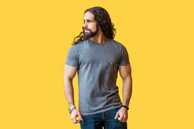 Porträt des groben hübschen bärtigen Modells des jungen Mannes mit dem langen gelockten Haar im grauen T-Shirt, das weg mit ernst stockfoto