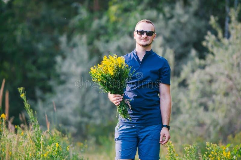 Porträt des gut aussehenden Mannes in der Sonnenbrille draußen mit gelben Blumen für sein Mädchen lizenzfreies stockbild