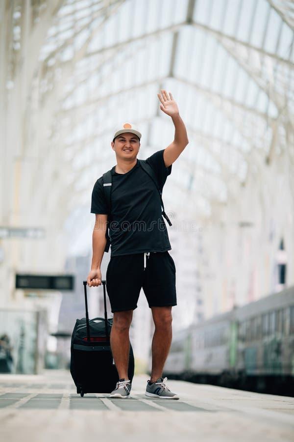 Porträt des gut aussehenden Mannes Handwellenartig bewegendes weg schauen und das Lächeln am Bahnhof anhebend stockfotografie