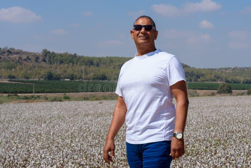 Porträt des hübschen älteren Mannes im Freien Sportlicher athletischer älterer Mann auf Hintergrund des Himmel- und Baumwollfelde lizenzfreie stockfotografie