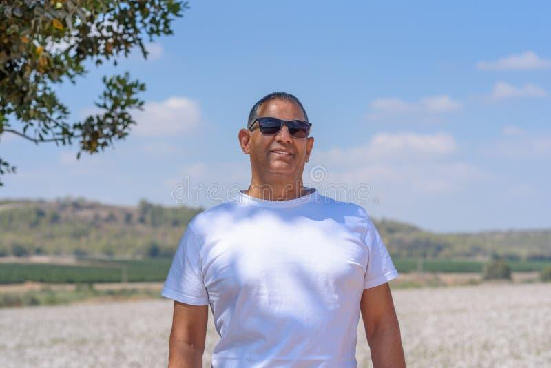 Porträt des hübschen älteren Mannes im Freien Sportlicher athletischer älterer Mann auf Hintergrund des Himmel- und Baumwollfelde lizenzfreies stockfoto