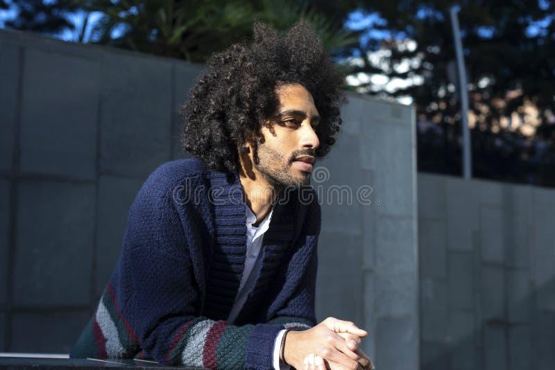 Porträt des hübschen afroen-amerikanisch Mannes in der zufälligen Kleidung, beim Lehnen weg schauend und lachen auf einem Zaun un lizenzfreie stockfotografie