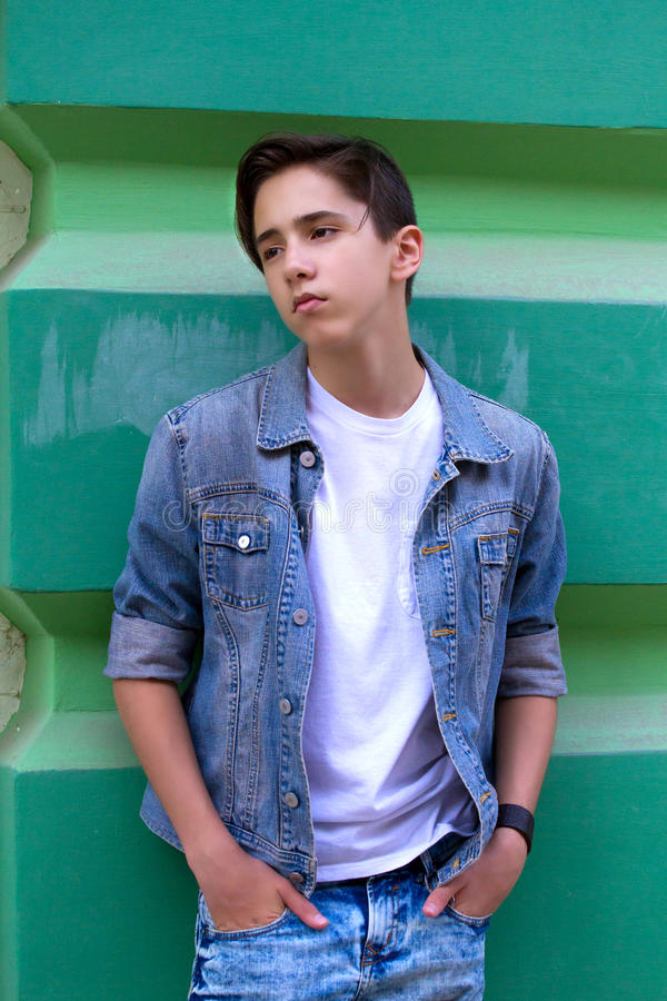 Porträt des hübschen attraktiven jugendlich Jungen, der draußen nah an der alten grünen Wand bleibt lizenzfreies stockfoto