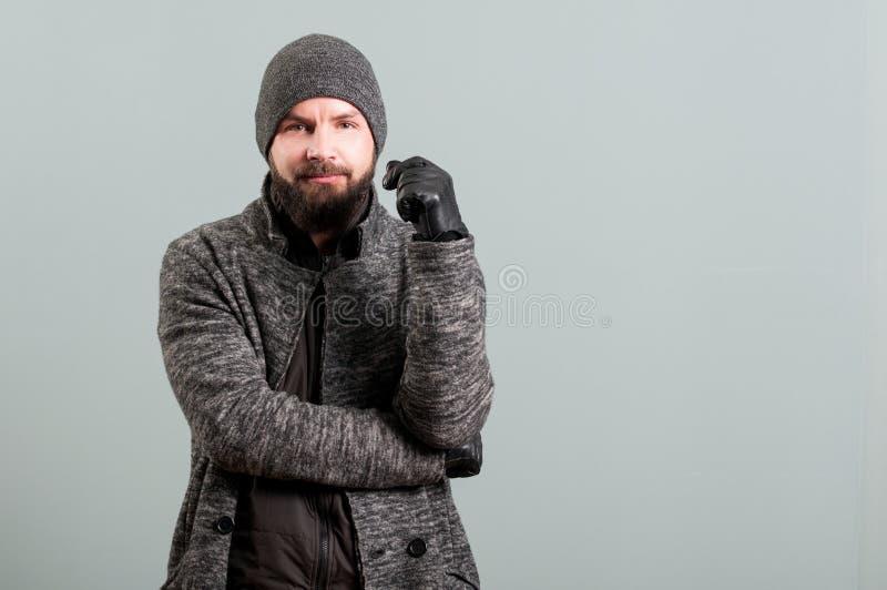 Porträt des hübschen bärtigen Mannes, der schwarze Lederhandschuhe trägt stockbild