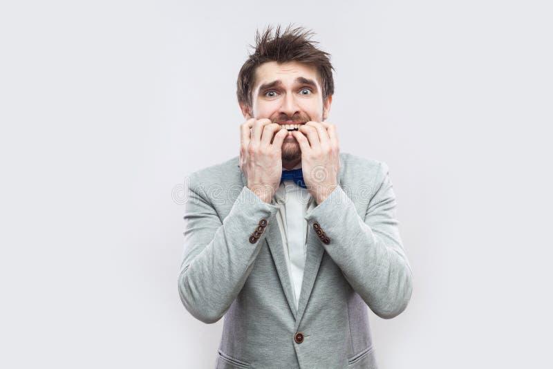 Porträt des hübschen bärtigen Mannes der Sorge im zufälligen grauen Anzug und in der blauen Fliegenstellung, nervös, seine Nägel  stockbild