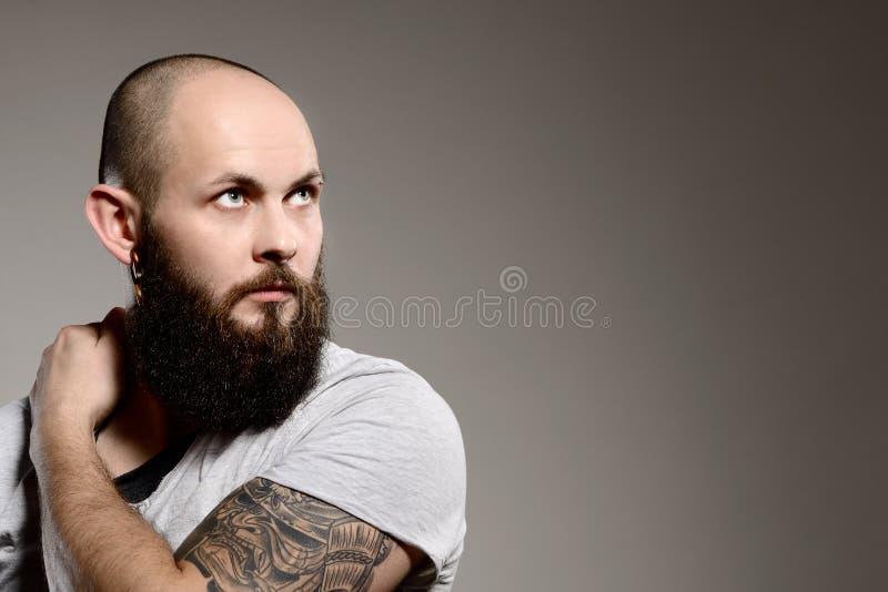 Porträt des hübschen bärtigen Mannes mit Tätowierungen stockbilder