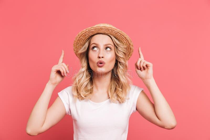 Portr?t des h?bschen blonden tragenden Strohhutes der Frau 20s, der aufw?rts Finger auf copyspace zeigt stockfoto