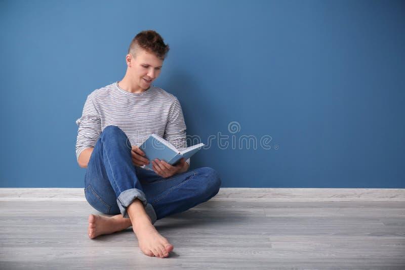 Porträt des hübschen Buches des jungen Mannes Lesebeim Sitzen auf Boden nahe Farbwand lizenzfreie stockbilder