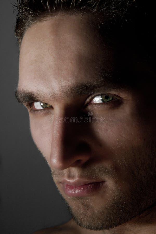 Porträt des hübschen dunklen Mannes, der im Studio aufwirft stockbild