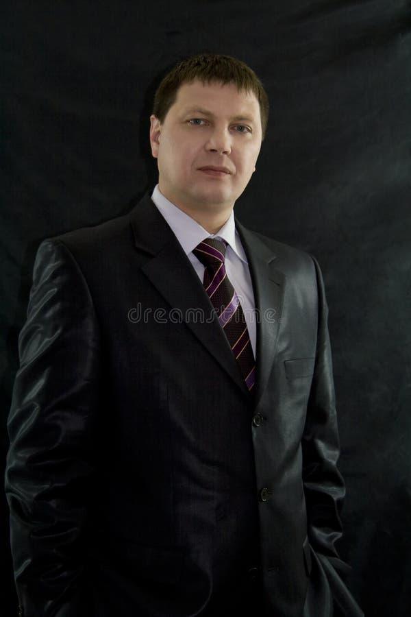 Porträt des hübschen Geschäftsmannes über schwarzem Hintergrund lizenzfreies stockfoto