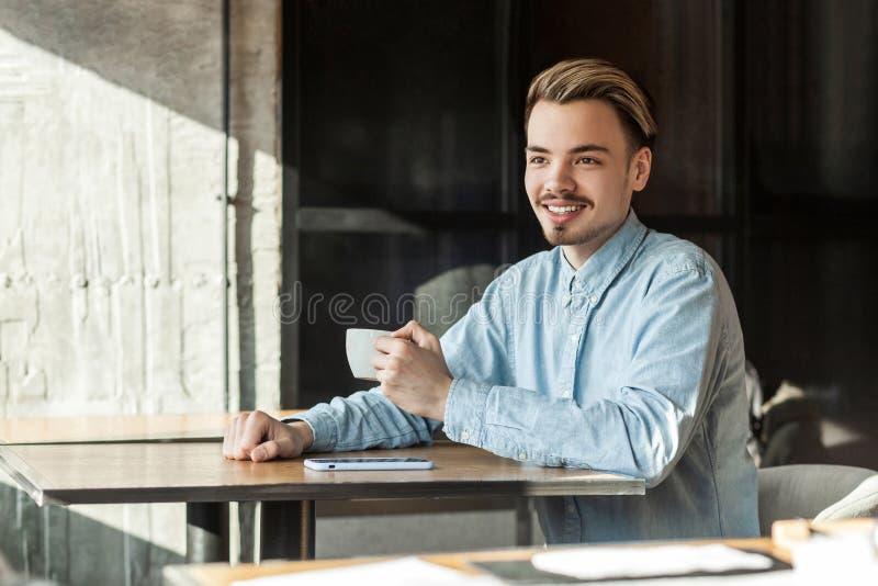 Porträt des hübschen glücklichen jungen Geschäftsmannes in sitzendem trinkendem Kaffee des blauen Denimhemdes, und weg schauen mi stockfotografie