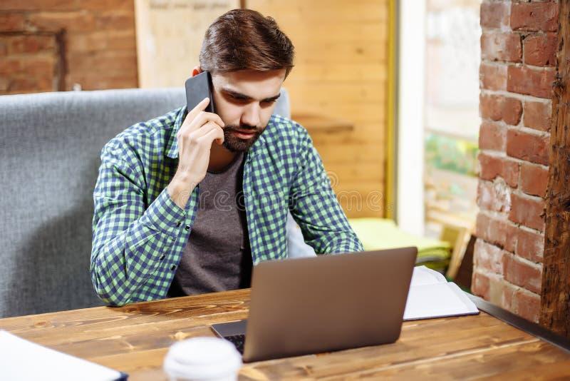 Porträt des hübschen jungen Geschäftsmannes, der am Schreibtisch mit Laptop sitzt und am Handy spricht schwarzes Telefon mit Empf lizenzfreies stockfoto