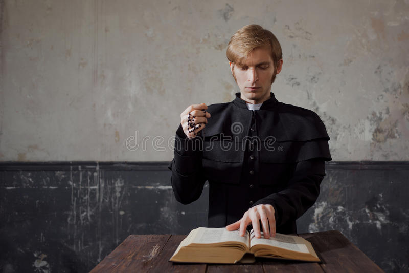 Porträt des hübschen jungen katholischen Priesters, der zum Gott betet stockfotos