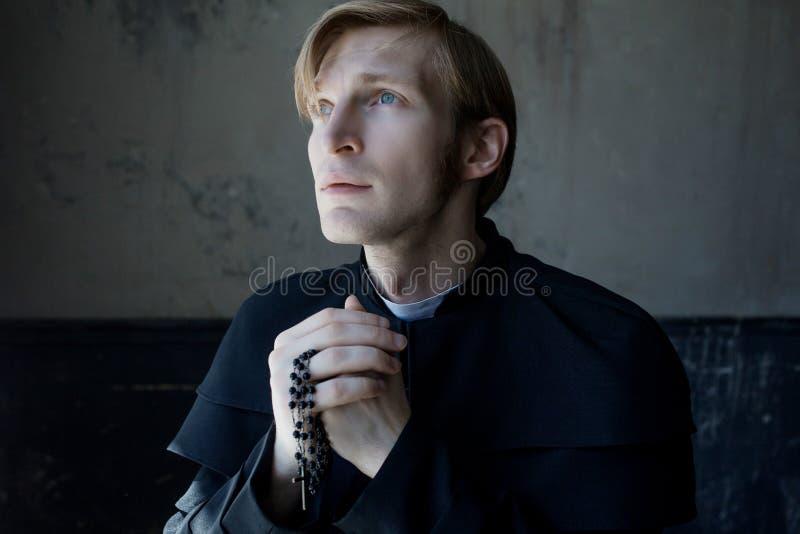 Porträt des hübschen jungen katholischen Priesters, der zum Gott betet stockbild