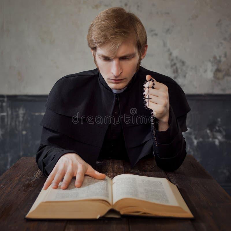 Porträt des hübschen jungen katholischen Priesters, der zum Gott betet lizenzfreies stockfoto