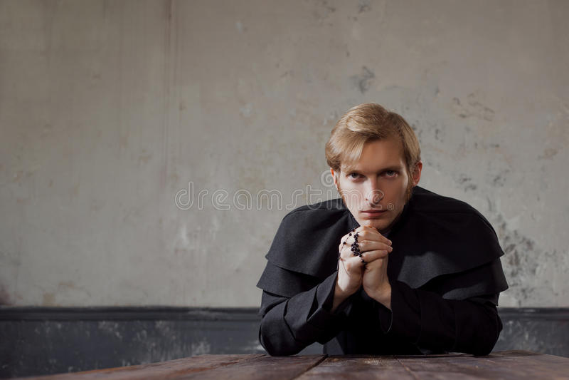 Porträt des hübschen jungen katholischen Priesters, der zum Gott betet Dunkle Art, Konzeptzweifel lizenzfreies stockfoto