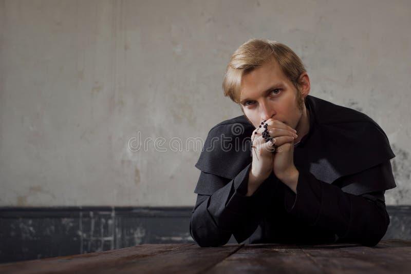 Porträt des hübschen jungen katholischen Priesters, der zum Gott betet Dunkle Art, Konzeptzweifel stockbild