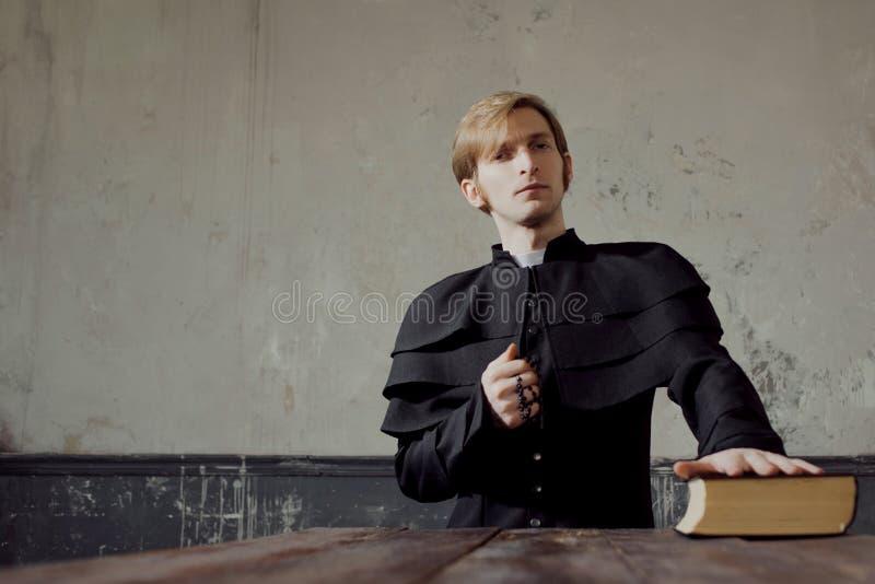 Porträt des hübschen jungen katholischen Priesters, der zum Gott betet Dunkle Art, Konzeptzweifel stockfotografie