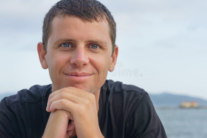 Porträt des hübschen jungen Mannes, der gegen einen Strand steht stockfotografie