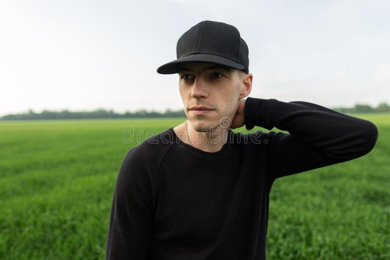 Porträt des hübschen jungen Mannes in der schwarzen stilvollen Kappe im modernen schwarzen Hemd auf dem Hintergrund des grünen Gr stockfoto