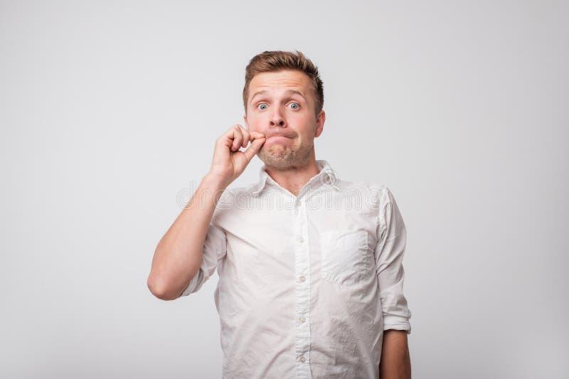 Porträt des hübschen jungen Mannes im weißen Hemd, das seinen Mund schließt, wird er gezwungen, Geheimnis zu halten, um jedermann stockfotografie