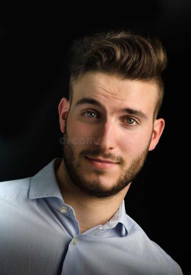 Porträt des hübschen jungen Mannes lokalisiert auf Schwarzem lizenzfreie stockfotografie