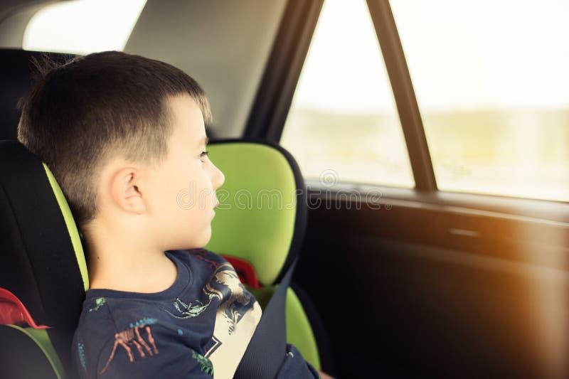 Porträt des hübschen Kleinkindjungen, der im Autositz sitzt Kindertransportsicherheit stockbild