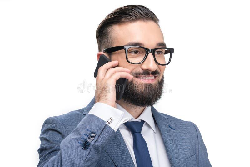 Porträt des hübschen lächelnden Geschäftsmannes in der grauen Klage unter Verwendung des Smartphone, lizenzfreies stockfoto