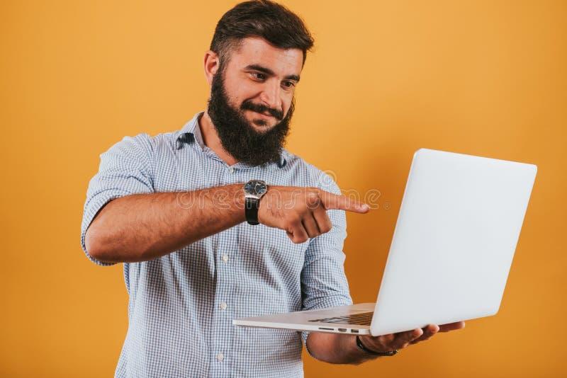 Porträt des hübschen lächelnden Mannes, der auf dem gelben Studiohintergrund aufwirft zur Kamera und macht lustige Gesichter loka stockfotos