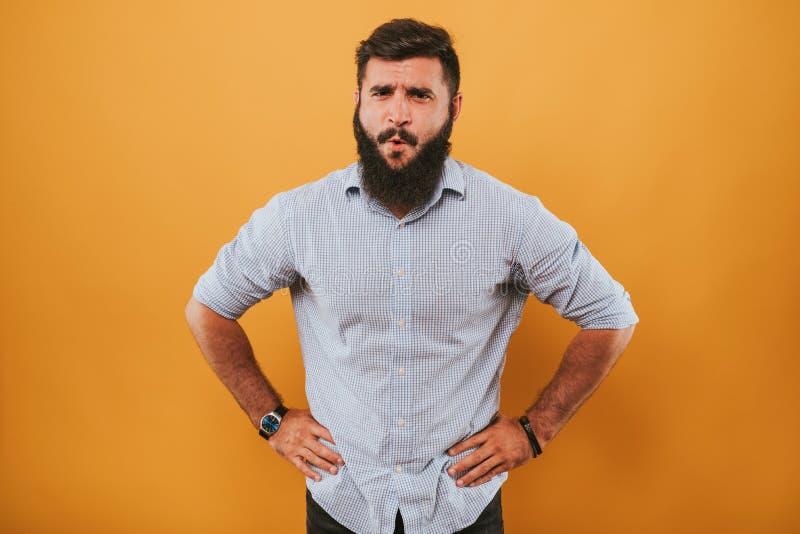Porträt des hübschen lächelnden Mannes, der auf dem gelben Studiohintergrund aufwirft zur Kamera und macht lustige Gesichter loka lizenzfreie stockfotos