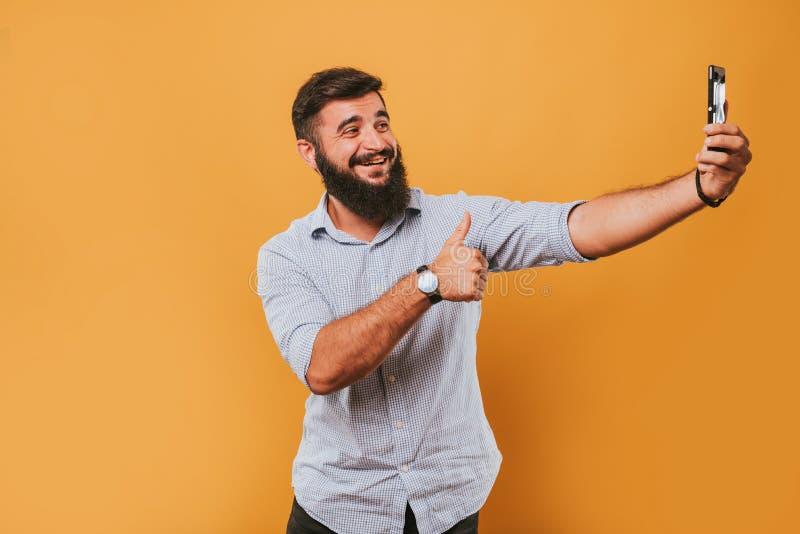 Porträt des hübschen lächelnden Mannes, der auf dem gelben Studiohintergrund aufwirft zur Kamera und macht lustige Gesichter loka stockbild