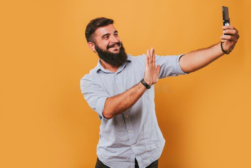 Porträt des hübschen lächelnden Mannes, der auf dem gelben Studiohintergrund aufwirft zur Kamera und macht lustige Gesichter loka stockbilder