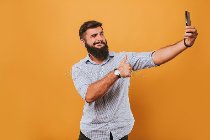Porträt des hübschen lächelnden Mannes, der auf dem gelben Studiohintergrund aufwirft zur Kamera und macht lustige Gesichter loka lizenzfreie stockfotografie