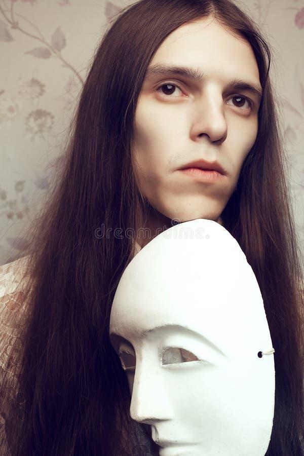 Porträt des hübschen langhaarigen Dichters mit einer weißen Maske lizenzfreies stockfoto