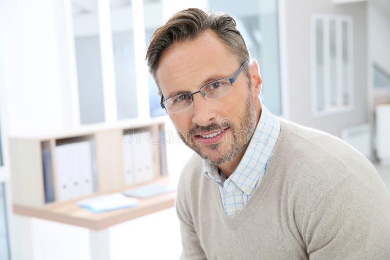 Porträt des hübschen Mannes von mittlerem Alter im Büro stockfoto