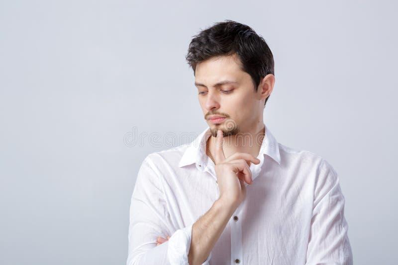 Porträt des hübschen nachdenklichen Brunettemannes im Hemd auf grauem backg stockbilder