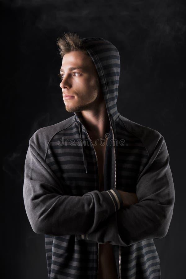 Porträt des hübschen starken jungen Mannes im dunklen Hoodie stockfoto