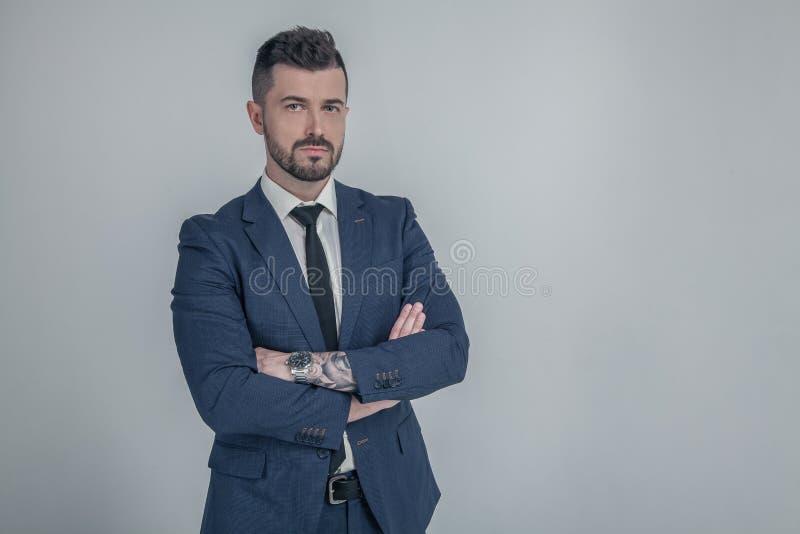 Porträt des hübschen strengen Arbeitgebers in der blauen Klagenstellung mit den gekreuzten Händen gegen grauen Hintergrund lizenzfreie stockfotografie