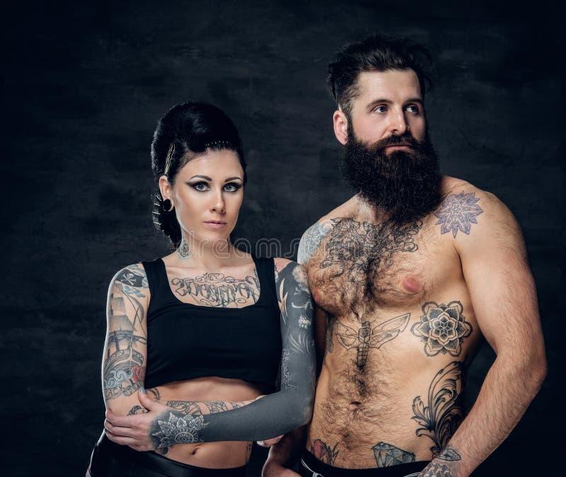 Porträt des hemdlosen, tätowierten bärtigen Mannes und der Brunettefrau mit Tätowierungstinte auf ihrem Torso stockfotografie