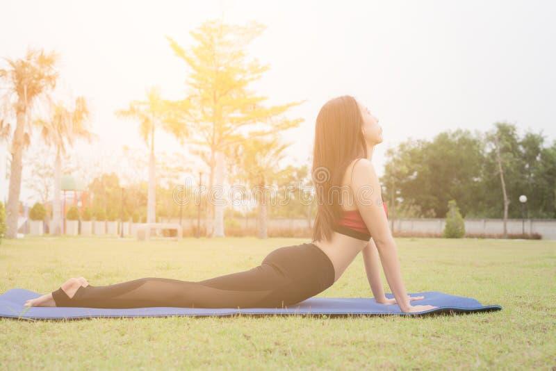 Porträt des herrlichen übenden Yoga der jungen Frau im Garten, asiatisch stockfoto