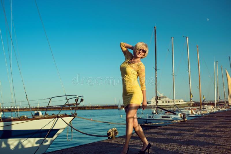 Porträt des herrlichen blonden lächelnden tragenden Gelbs der Frau von mittlerem Alter fest-passte das Spitzekleid und -Sonnenbri stockfotografie